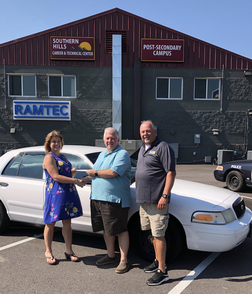 Director Vicki Carrington and Commander Randy Carson receiving the donation of a police car from Dr. Donald Locasto.
