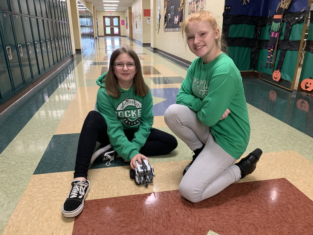 Students test their robot creation in the hall.